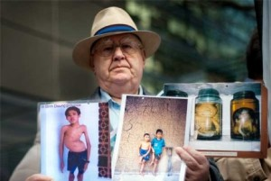 Len holding up pictures of young victims of Agent Orange