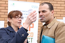 Member of the public using a carbon monoxide monitor to see how much of this poisonous gas is trapped in his blood.