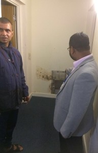 Cllr Miah inspects isrepair in the block with one of the residents.