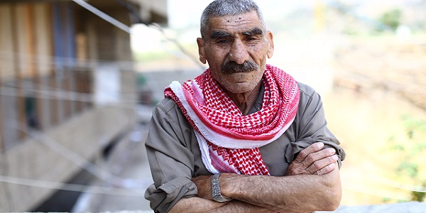 Older man with red keffiyeh: Kassar, from Hama fled with his 11 children, crossing into Lebanon. He can't work due to injury, and his wife is the breadwinner now. He sits in the square of a half built university all day, waiting for her to come home. Southern Lebanon 06/17.
