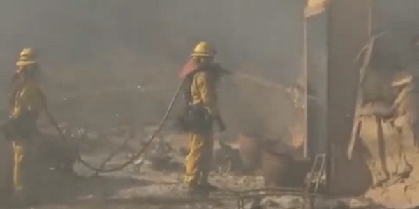 Firefighters damp down a burned out structure in the California wildfires.