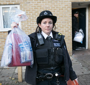 Police officer displays recovered items during a drugs raid in Shadwell, December 2017
